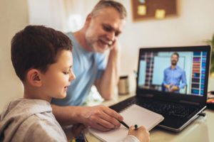 Father helps young son with distance learning on computer.