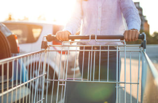 Woman with shopping cart loading groceries in car