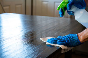 Man in gloves wiping down tabletop with disinfectant