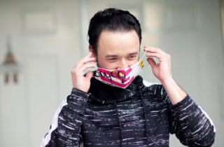 man putting on cloth face mask