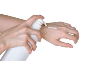 Person applying moisturizer to dry hands.