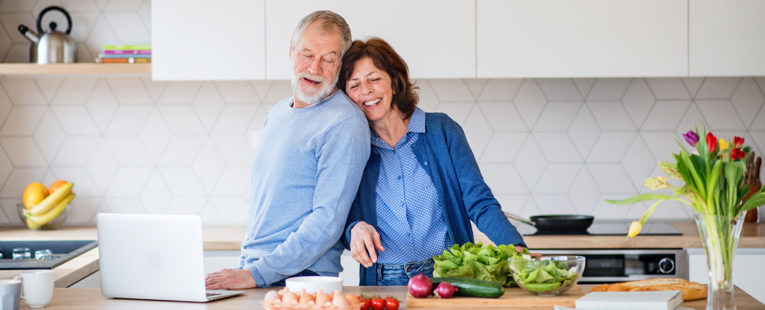 Senior couple cooking healthy food in kitchen.