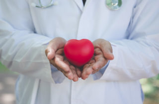 Cardiologist in white coat with toy heart.