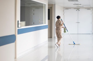 Facilities employee mopping office floor