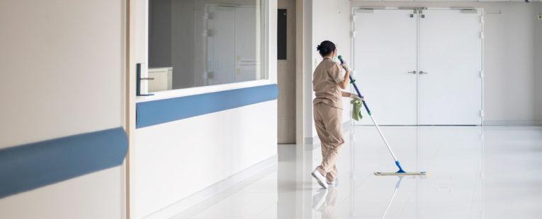 Facilities employee mopping office floor