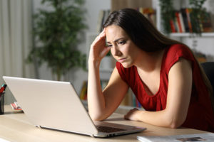 Young concerned woman reading news on laptop.