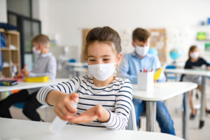 masked child washes their hands in school