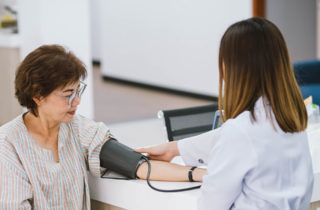 Female with hypertension getting blood pressure checked by health care provider.