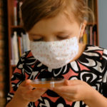 6-year-old coughs into petri dish with a face mask on in germ experiment