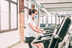 Athletic young masked woman riding an exercise bike in gym.