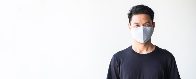 Masked Asian-American male wearing a t-shirt and smiling.