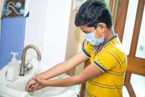boy wearing mask washing hands