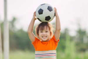 young boy holds soccer ball on head