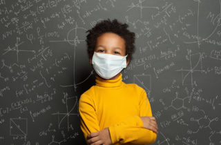 Young African-American child in yellow shirt standing in front of chalkboard with chemistry formulas.