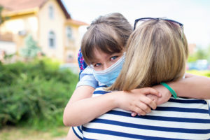 Young masked girl hugging mother before school