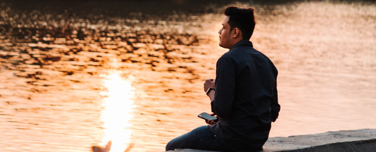 Young man sitting by a river staring off into the distance