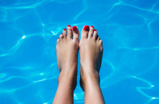 Woman's feet in a pool of water.