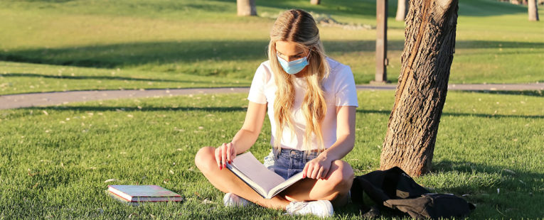 Young masked woman college student reading textbook outdoors.
