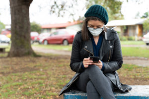 Young masked woman college student reading her phone in a park.