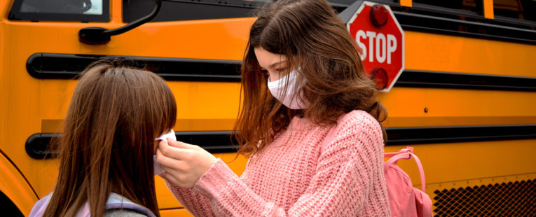 Young sisters help each other put on face masks before boarding school bus.