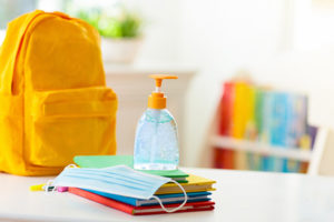 Kitchen counter top with yellow backpack, school books, mask and hand sanitizer.