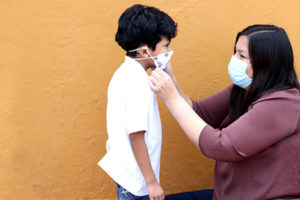 Young Latino-American mother wearing a mask outfitting her son with a mask before school.