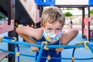 Young masked boy playing on playground equipment.