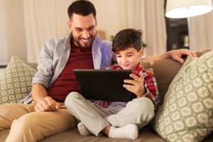 Father and son using a tablet on a couch.