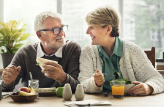 male and female seniors eating healthy food smiling at each other