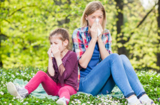 a small girl and a woman suffer with allergies outside