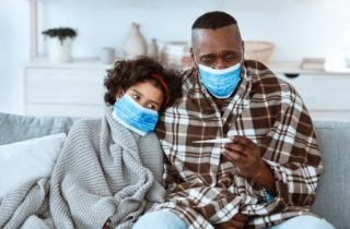 sick father and daughter in blankets wearing masks while the father holds a thermometer