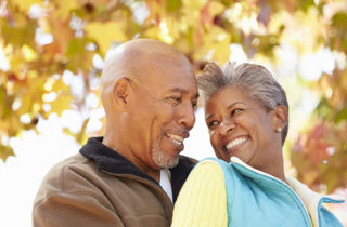 Active African-American senior couple in a warm embrace on an autumn day.
