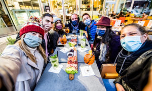 Group of friends celebrating the holidays while wearing masks
