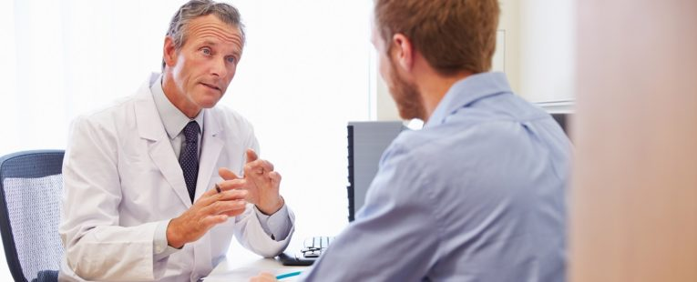 male physician sitting down and conversing with a male patient