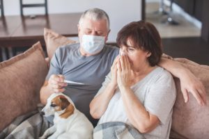 masked husband takes his wife's temperature on the couch with the family dog in their laps