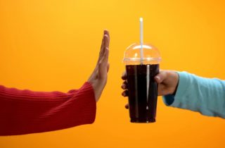 one hand offers another a soda while the other gesture rejection