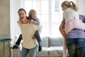Young family playing in living room to avoid pandemic fatigue