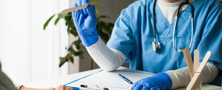 Doctor at desk in face mask and gloves with tongue depressor; patient hands visible in foreground