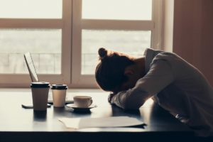 visibily fatigued woman slumped over her desk surrounded by cups of coffee