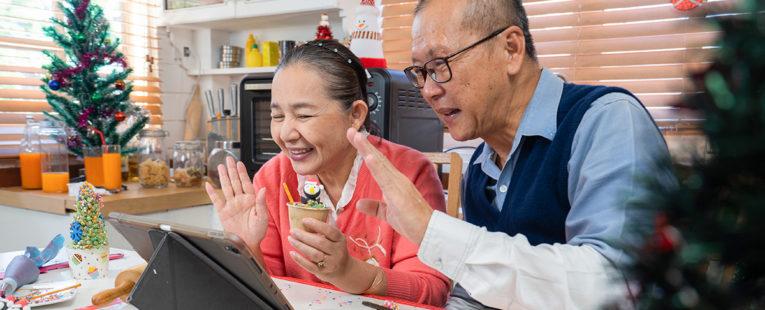 Senior couple waving at iPad during Christmas