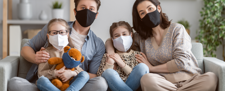 family of four wearing masks on a couch