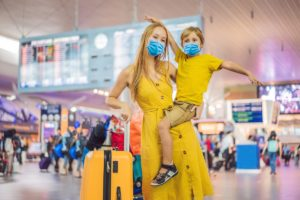 mother and a son wearing masks with a suitcase at a busy airport