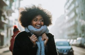 young woman with afro and scarf takes a winter walk