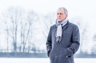 senior man stands solemnly outside in a coat and scarf during winter