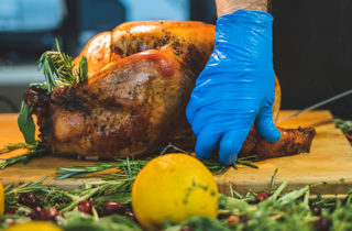 Man with blue kitchen gloves carves oven-baked Thanksgiving turkey on cutting board with lemons and rosemary in foreground