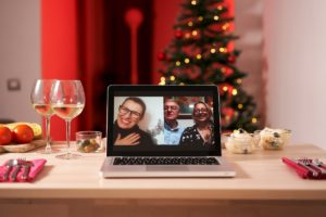 table set for christmas dinner with a laptop set as a guest with people on screen
