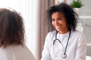 female doctor smiles as they meet with a female patient