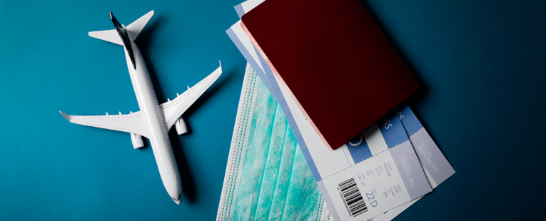 toy plan next to a passport plane ticket and mask