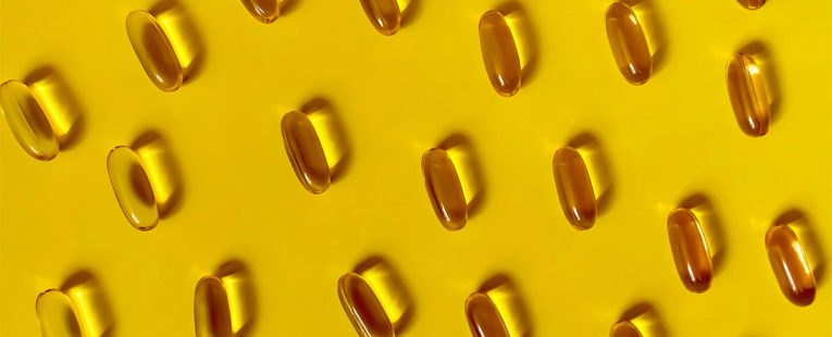 Vitamin D capsules on yellow background.