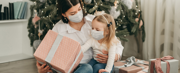 woman holds a child on her lap with a present both wearing masks in front of a Christmas tree